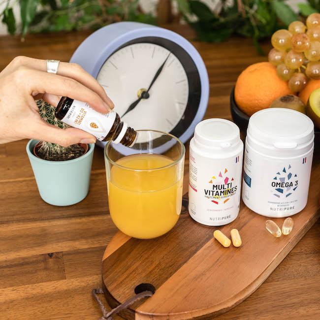 vitamine D3 k2 versé dans un verre de jus d'orange
